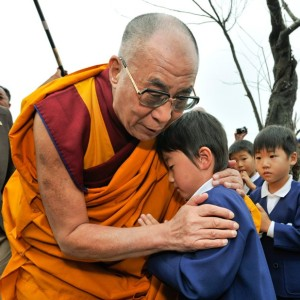HHDL comforts a young boy who lost his parents to the tsunami